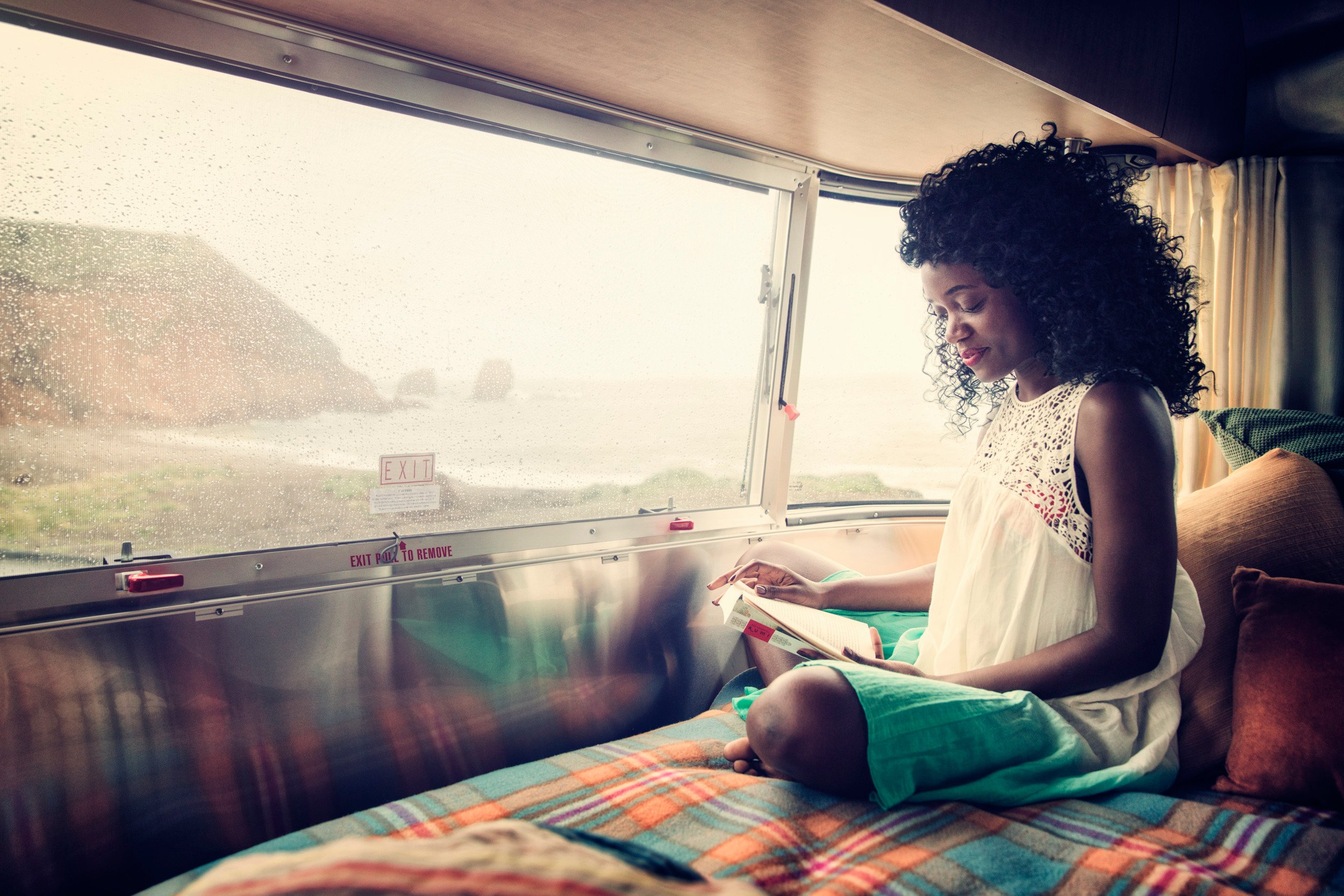 Dometic, caravan, RV, camper, climate, woman, reading, cozy, blanket, inside, ocean, view, window